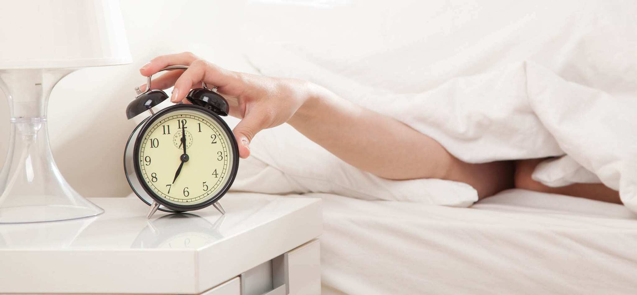 Hand under blanket reaching out for alarm clock, shallow depth of field focus on foreground